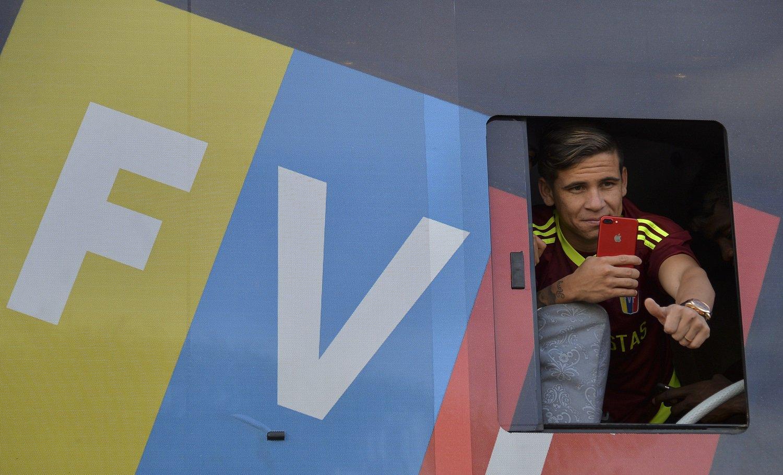 El jugador venezolano de la selección sub-20 Yeferson Soteldo, subcampeón de la Copa Mundial Sub-20 en Corea del Sur, mira a los aficionados a través de la ventana del autobús durante una caravana en ruta para una ceremonia de bienvenida en el Estadio Olímpico de la Universidad Central de Venezuela, En Caracas, el 13 de junio de 2017. / AFP PHOTO / LUIS ROBAYO