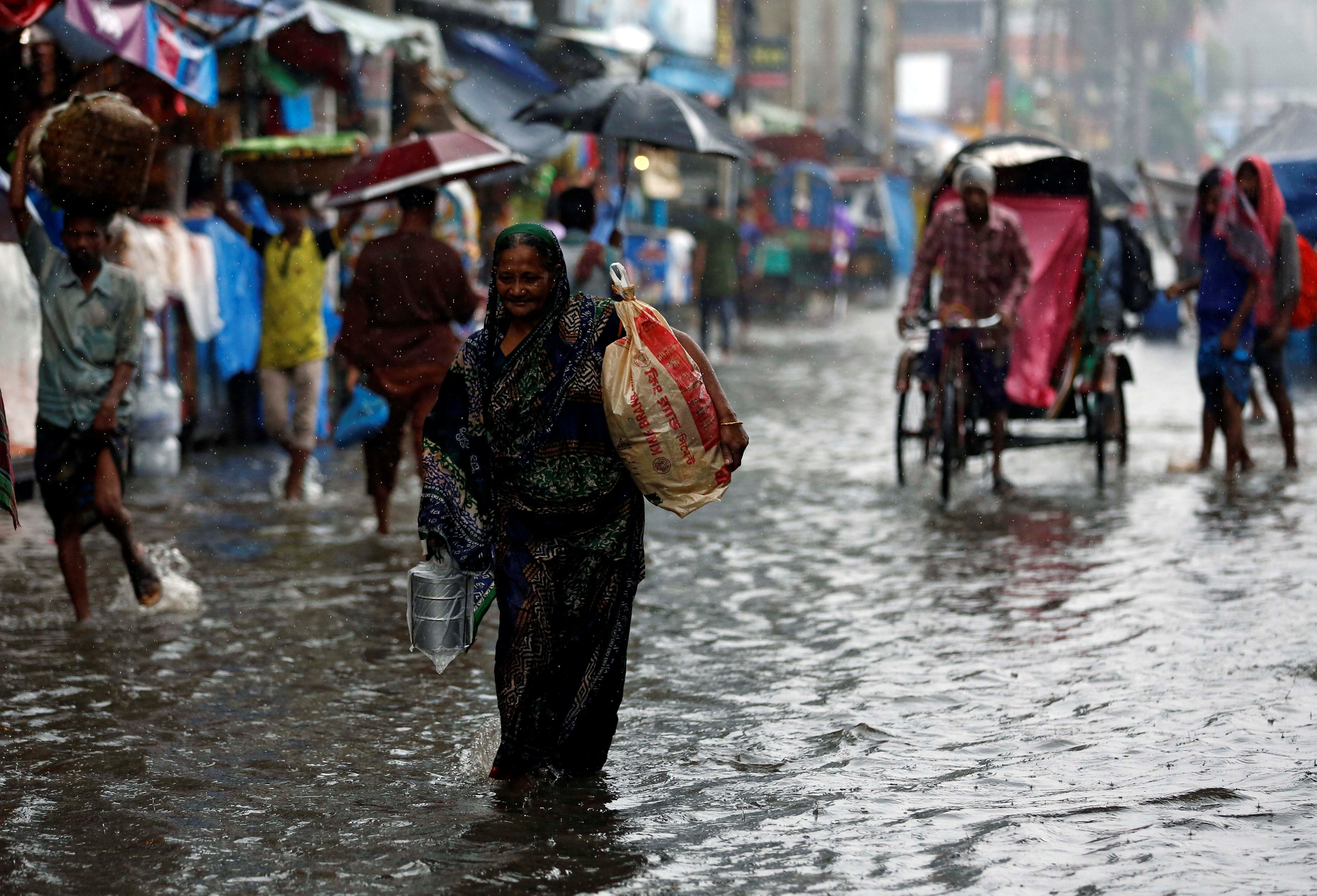 A woman with bags walks along a street as roads are flooded due to heavy rain in Dhaka, Bangladesh July 26, 2017. REUTERS/Mohammad Ponir Hossain