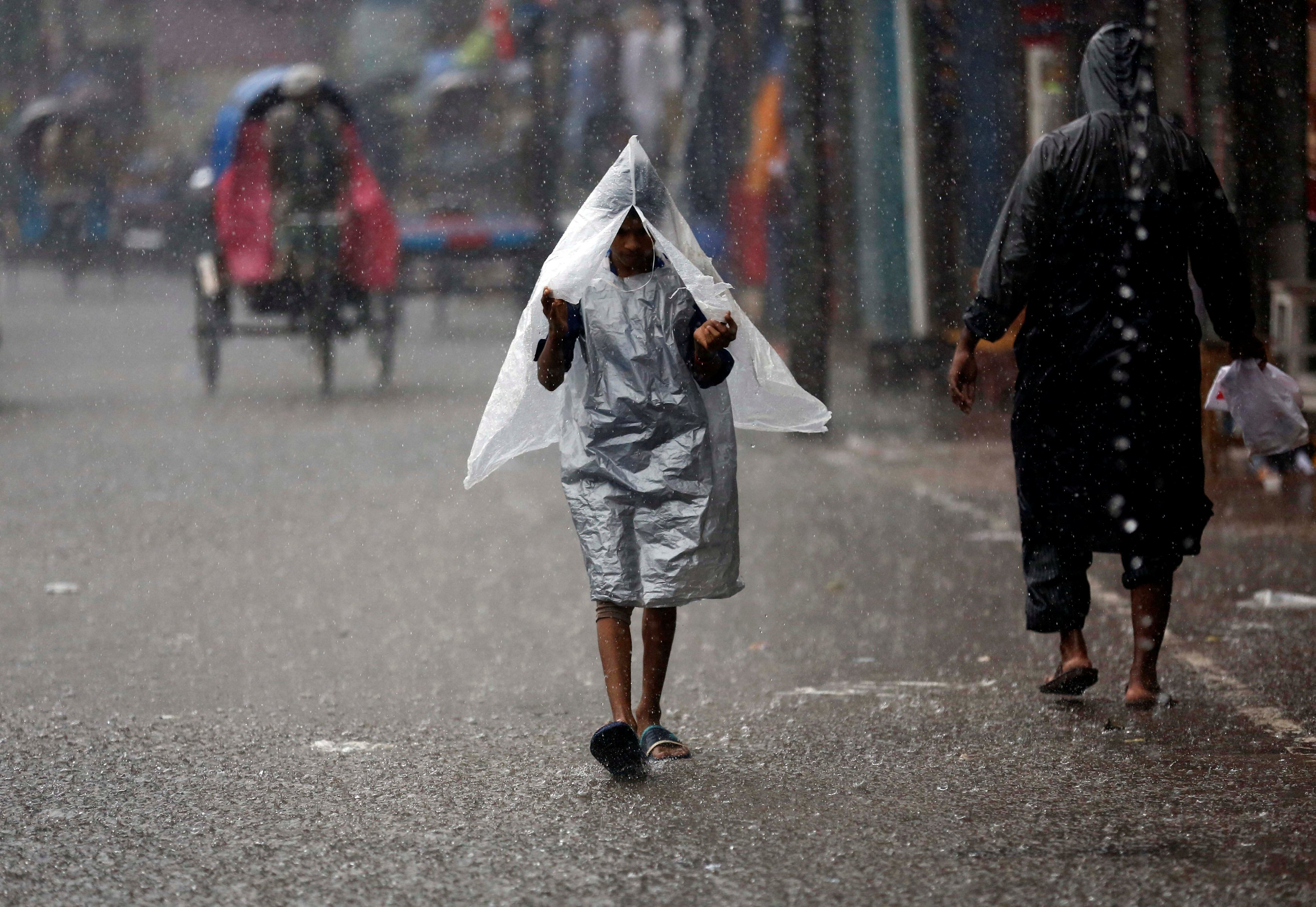A boy covers his body with polythene sheet while walking on the road during heavy rain in Dhaka, Bangladesh July 26, 2017. REUTERS/Mohammad Ponir Hossain